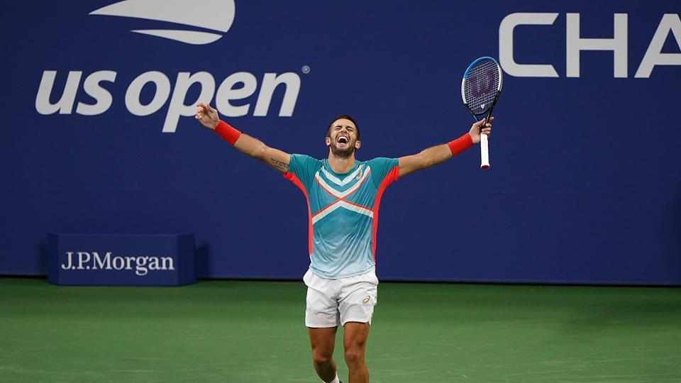Un jugador que participó en la US Open levanta los brazos en señal de victoria.